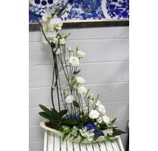 Комбинированная настольная композиция из горшечного растения и свежесрезанных цветов в керамическом кашпо. Состав: высаженная в грунт орхидея фаленопсис, эустома, симфорикарпус, альстромерия, гортензия, лист стрелиции.