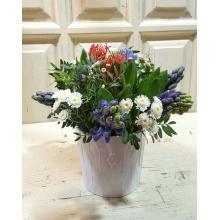 Керамическе белое кашпо с 7 синими гиацинтами, кустовой хризантемой и экзотической ятрофой.