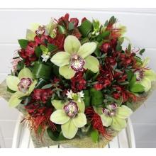 Большой букет из зеленых цветов цимбидиума (орхидеи), альстромерии, орнитогалума, зелени с декоративными вставками, упаковкой и атласными и капроновыми лентами