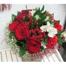 Праздничный букет из красных роз, гиперикума, красной гвоздики, гипсофиллы, белой альстромерии, зелени в натуральной упаковке из сизаля с лентами.
