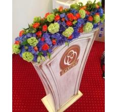 Композиция, повторяющая форму трибуны из гортензии, кустовых роз, калины, альстромерии, зелени.