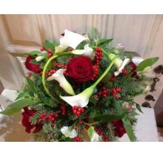 Букет из белых калл, красных роз, альстромерии, ягод илекса, веток пихты без упаковки с большим атласным бантом.