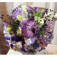Букет из орхидеи Ванды, ягод калины, альстромерии на каркасе из сухоцветов в виде венка с зеленью и лентами.