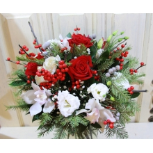 Яркий букет из белых орхидей, красных роз, ягод илекса, эустомы, веток брунии, пихты в натуральной упаковке с лентами.
