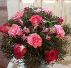 Букет из розовых роз, розовых гвоздик, альстромерии, зелени в натуральной упаковке из сизаля с летнами.