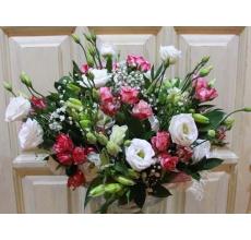 Нежный букет из белой эустомы, розовой кустовой розы, белой альстромерии, гипсофиллы, зелени в натуральной упаковке с лентами.