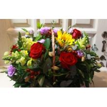 Корзина из подсолнуха, красных роз, антириниума, альстромерии, эустомы, гиперикума, зелени.