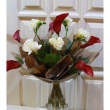 Букет из красно-бордовых калл и белой фрезии в упаковке из бумаги крафт с лентой.