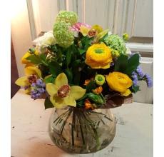 Букет весенних ранункулюсов, орхидей, разноцветных гвоздик, калины, орнитогалума, статицы, зелени в упаковке из крафт-бумаги.