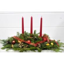 Настольная композиция из веток пихты, если, декоративных шаров, ленты, сухофруктов, шишек, трех красных свечей.