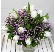 Букет из 15 белых тюльпанов с розовой гипсофиллой, зеленью в упаковке из фетра и белой органзы.