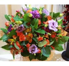Букет из оранжевых кустовых роз, фиолетовой эустомы, гиперикума, альстромерии, зелени в натуральной упаковке с лентами.