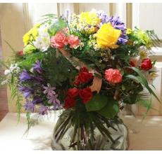 Летний транспарентный букет из голубого агапантуса, скабиозы, красной кустовой розы, желтой крупной розы, кустовой хризантемы, оранжевой гвоздики, фисташковой гвоздики, матрикарии, восковника, аспарагуса, фисташки, другой зелени