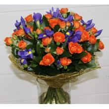 Букет из ярких кустовых роз с ирисами, зеленью в натуральной упаковке с лентами.