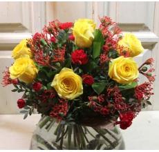 Яркий букет из экзотической красной ятрофы, сортовых желтых роз, кустовой гвоздики, зелени в упаковке из бумаги крафт с лентой.