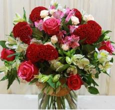 Большой букет из бархатной экзотической целлозии, малиновых роз, кустовых роз, альстромерии, зелени в натуральной упаковке с лентами.