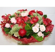 Букет из персиковой кустовой розы, красных ранункулюсов, гиперикума, альстромерии, трахелиума, зелени в натуральной упаковке с лентами.