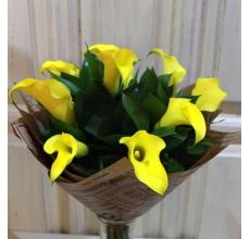 Букет из 9 ярко-желтых калл с рускусом в упаковке из бумаги крафт с флористической лентой.