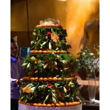 Состав: метал. конструкция на колесиках, юбка текстиль, лилия лонгифлорум, герберы, зелень, мандарины. Цветовое и цветочное оформление торта может быть изменено в соответствии с общим концептом мероприятия.
