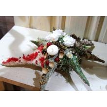 Композиция из горизонтальных елок из соломы с декоративными новогодними элементами, свечой и живыми цветами.