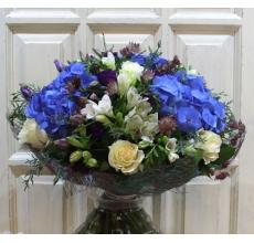 Большой букет из голубой гортензии, белых роз, нежной фрезии, альстромерии, эустомы, астранции, разнообразие экзотической зелени в натуральной упаковке из сизаля с лентами. Диаметр букета от 45 см.
