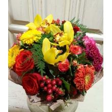 Яркий букет из желтой орхидеи, желтых и оранжевых махровых гербер, малиновой, желтой и оранжевой целлозии, малиновой и оранжевой кустовой розы, гиперикума, алых роз, зелени в упаковке из бумаги крафт