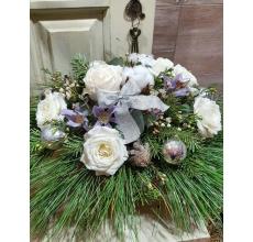 Настольная новогодняя композиция в плетеном кашпо. Состав: белая кустовая роза, хлопок, шишки, клематис, восковник, кедр, шары.