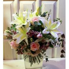 Букет из бело-лимонной лилии, восковника, нежной розовой розы, эустомы, зелени в натуральной упаковке с лентами.