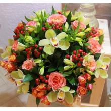 Букет из цветов зеленой орхидеи цимбидиум, коралловых роз, кустовых роз, альстромерии, гиперикума, зелени в натуральной упаковке с лентами.