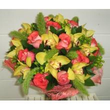 Большой орнаментальный букет из орхидеи цимбидиум, роз, сетарии, зелени в натуральной упаковке из сизаля с атласной лентой.