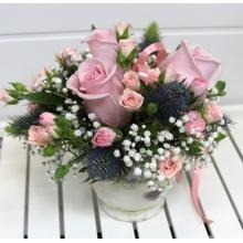Композиция в небольшой керамической вазе с розовами розами, ирингиумом, кустовыми розами и атласной лентой.