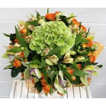 Букет из зеленой гортензии, орхидей цимбидиум, альстромерии, оранжевой кустовой розы, зелени в натуральной упаковке с лентами