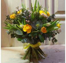 Букет весенних ярких ранункулюсов, сортовых тюльпанов, восковника, эвкалипта, зелени с лентами и бантом.