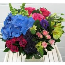 Букет из голубой гортензии, малиновых роз, кустовых роз, антириниума, орнитогалума, трахелиума, альстромерии, эустомы с зеленью с атласной лентой.