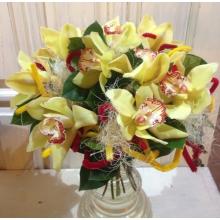 Букет из цветов орхидеи и зелени на декоративном каркасе с разноцветными декоративными элементами.