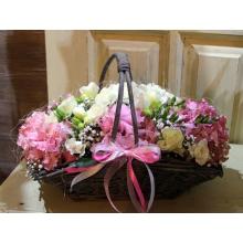 Низкая настольная европейская корзина из двух больших цветов гортензии, белой кустовой розы, фрезии, гипсофиллы с бантом из атласных и капроновых лент