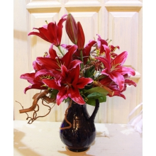 Букет из бордовой сортовой лилии с ветками корилуса, лимониума, астранцией, салалом без упаковке с лентами.