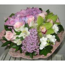 Букет из лиловой гидрангеи, сирени, орхидей, розовых роз, альстромерии, фрезии, зелени в натуральной упаковке с лентами.