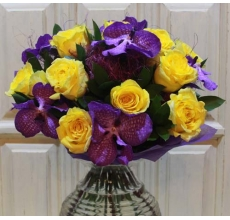 Букет из ярких желтых сортовых роз, орхидей сорта ванда, зелени, сизаля в упаковке из фетра с лентами.