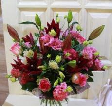 Букет из темно-бордовой лилии, альстромерии, эустомы, роз с зеленью в натуральной упаковке с лентами.