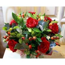 Букет из красныз роз, шиповника, скиммии, зелени в натуральной упаковке с лентами.
