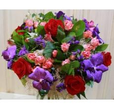 Праздничный букет из красных роз, орхидеи ванды, кустовых роз, статицы, альстромерии, зелени, сизаля в натуральной упаковке с лентами.
