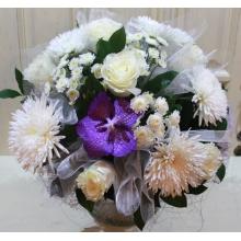 Праздничный букет из белых одноголовых хризантем (Анастасия), белых роз, кустовой хризантемы, орхидеи ванды с вставками из органзы в натуральной упаковке с атласными лентами.