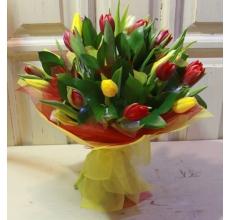 17 красных и желтых тюльпанов с зеленью в разноцветной упаковке из фетра с капроновым бантом.
