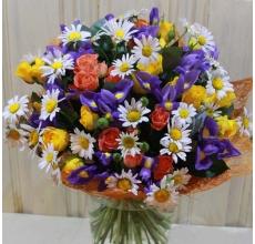 Букет из желтых и оранжевых кустовых роз, синих ирисов, ромашек, зелени в натуральной упаковке с лентами. Ромашки могут быть заменены на матрикарию по сезону.