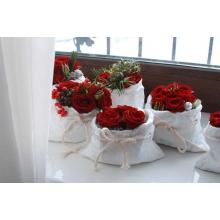 Настольное украшение Мешочек с кустовыми розами, пихтой, шишками, конфетами ферреро, илексом станет приятным милым подарком, чтобы зимний день стал теплее и вкуснее.