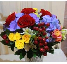 Летний букет из голубой гортензии, красных роз, гиперикума, желтой и оранжевой кустовой розы, альстромерии, зелени без упаковки с лентами.
