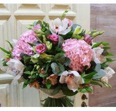 Букет из розовых гортензий, орхидей, эустомы, альстромерии, зелени в натуральной упаковке с лентами.