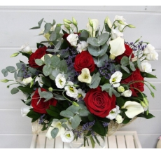 Элегантный букет из белых калл, белой эустомы, красных роз, веток эвкалипта, зелени в натуральной упаковке из сизаля с лентами.