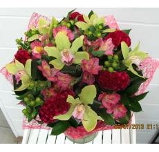 Букет экзотических цветов из целлозии, орхидеи цимбидиум, альстромерии, гиперикума в натуральной упаковке с атласными лентами.